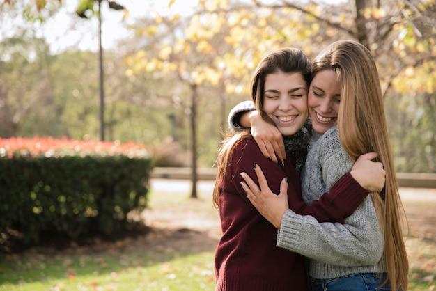Средний снимок двух обнимающихся молодых женщин в парке Бесплатные Фотографии