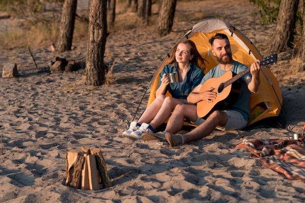 Счастливая пара в поход и играет на гитаре Бесплатные Фотографии