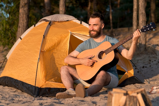 Мужчина играет на гитаре у палатки Бесплатные Фотографии