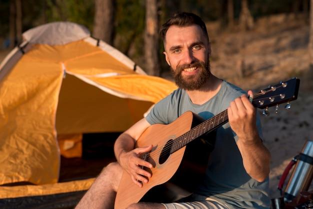 Гитарист смотрит в камеру у палатки Бесплатные Фотографии