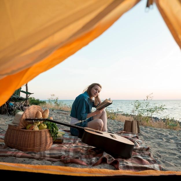 Женщина читает книгу перед палаткой Бесплатные Фотографии
