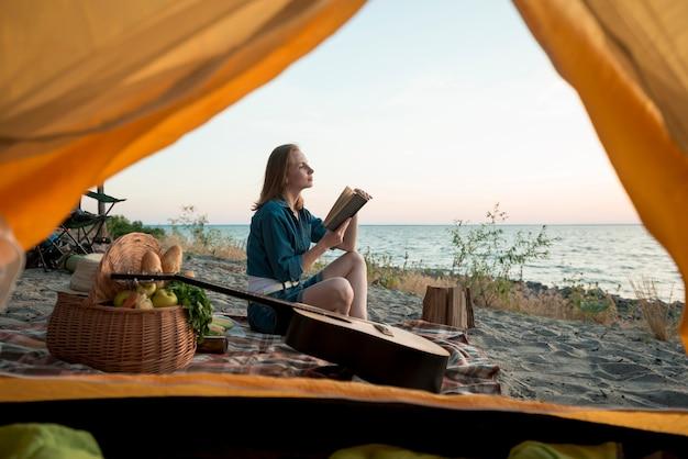 Женщина читает книгу на одеяле для пикника Бесплатные Фотографии