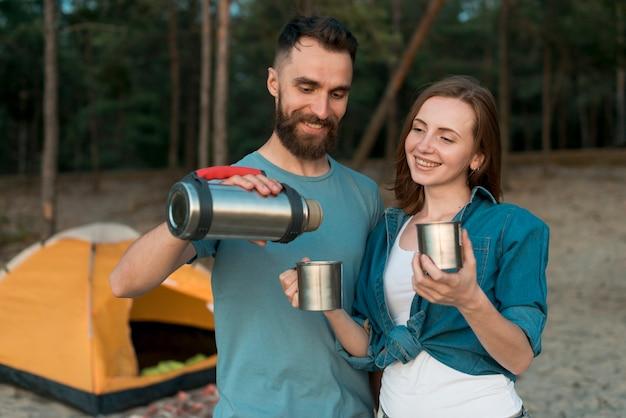 Стоящая пара наливает чай и улыбается Бесплатные Фотографии