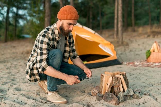 身をかがめるヒップスター照明キャンプファイヤー 無料写真
