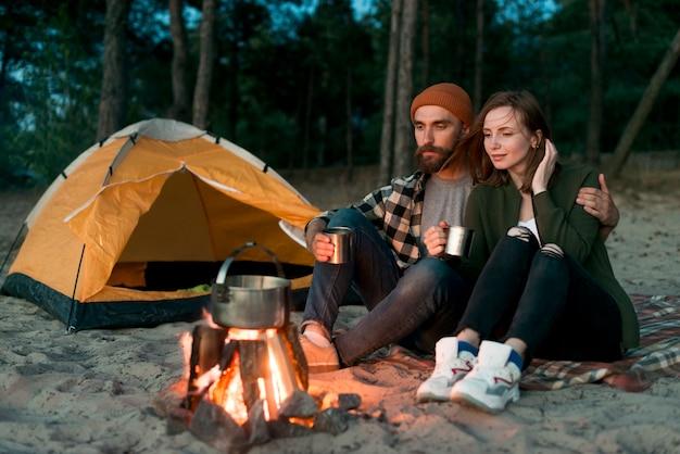 キャンプファイヤーで一緒に飲むキャンプのカップル 無料写真