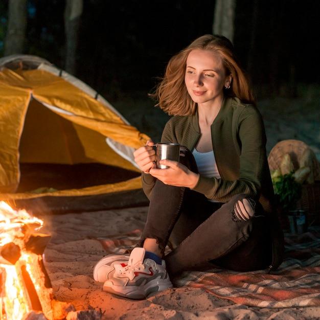 Сидящая девушка пьет у костра Бесплатные Фотографии