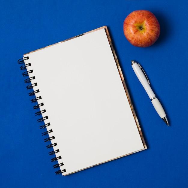 暗い青色の背景にアップルとモックアップメモ帳 無料写真
