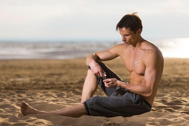 男は座っていると日焼け止めローションを適用する 無料写真