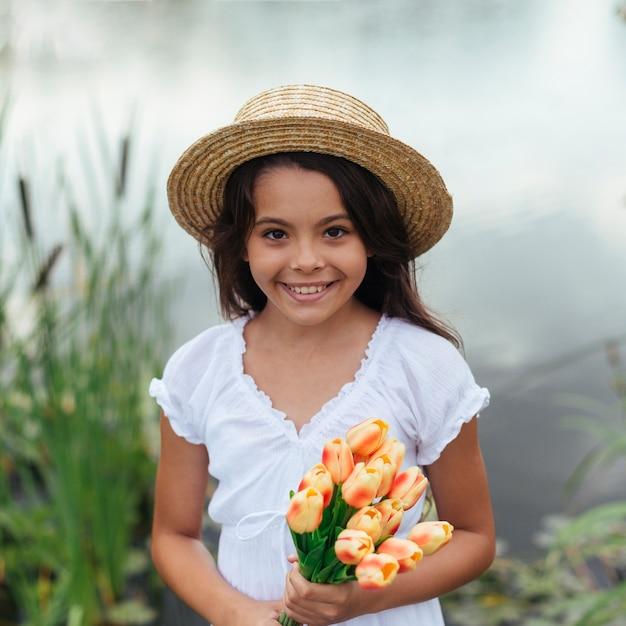 湖のそばで花を持ってきれいな女の子 無料写真