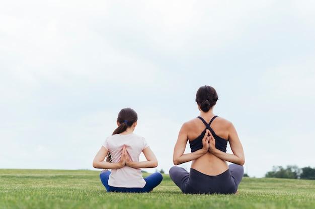 母と娘の後ろから瞑想 無料写真