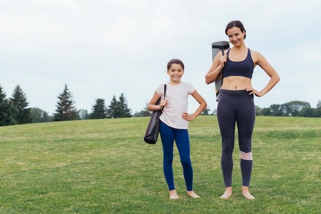 母と娘のヨガマットを運ぶ 無料写真