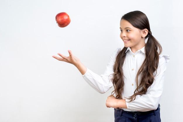 遊び心のあるヒスパニック女子高生投げアップル 無料写真