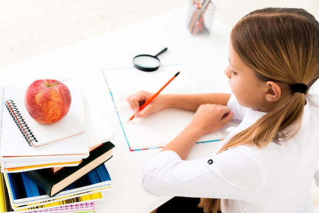 制服を着て机で勉強してかわいい女の子 無料写真