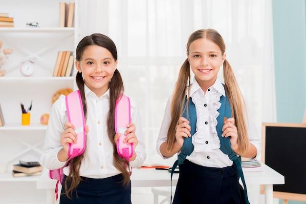 Симпатичные школьницы с рюкзаками, стоя в классе Бесплатные Фотографии
