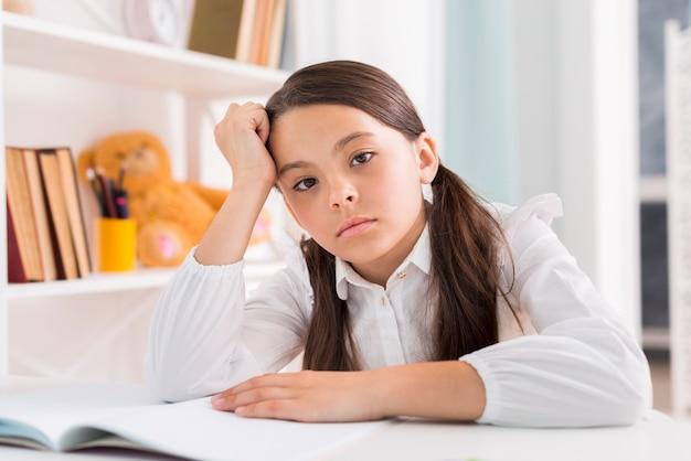 机で宿題をしている疲れている女子高生 無料写真