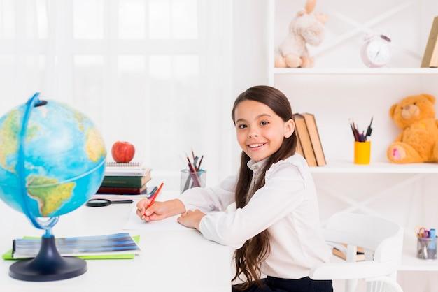 制服を着て自宅で勉強している女子高生の笑顔 無料写真