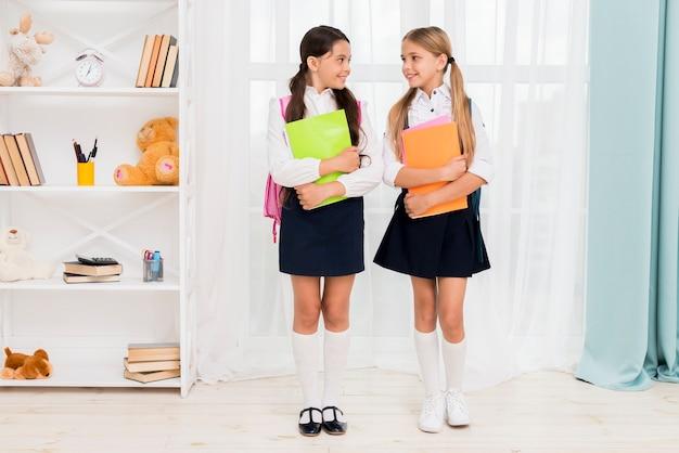Улыбающиеся школьники с рюкзаками стоят в квартире и смотрят друг на друга Бесплатные Фотографии