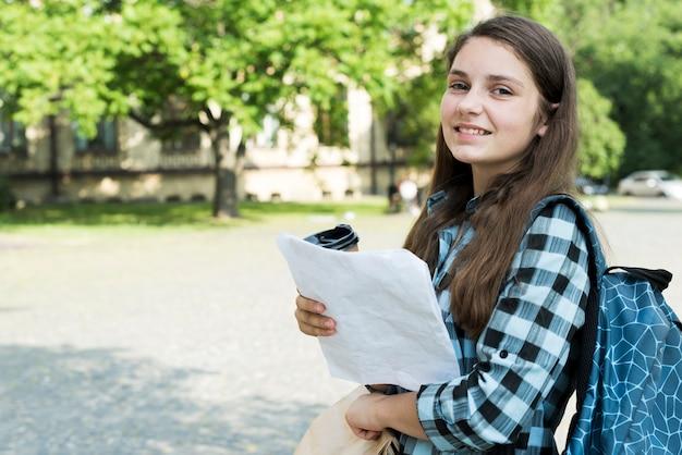 メモを保持している学校の女の子の側面図ミディアムショット 無料写真