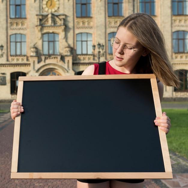 ミディアムショット高校生の女の子が黒板を探して 無料写真