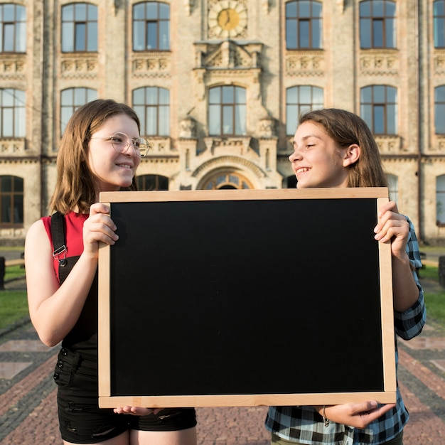 ミディアムショット高校生の女の子が黒板を保持 無料写真