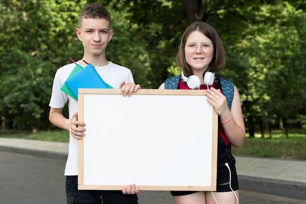 ホワイトボードを保持しているミディアムショットの高校生 無料写真