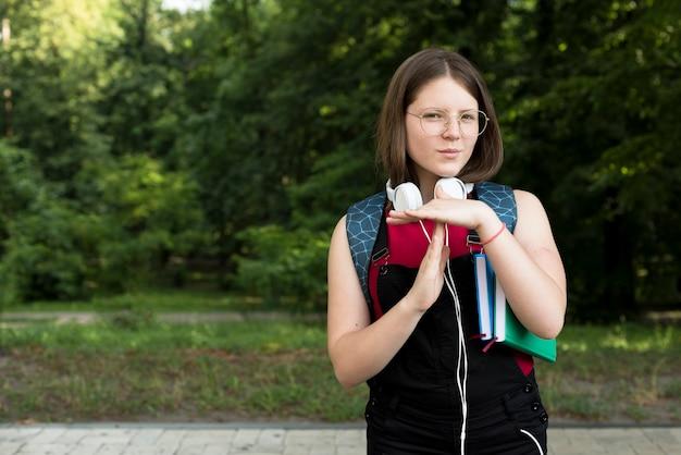 タイムアウトのサインを保持している高校の女の子のミディアムショット 無料写真