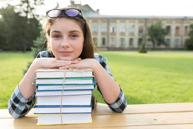 本の頭を休んで高校の女の子の肖像画を間近します。 無料写真
