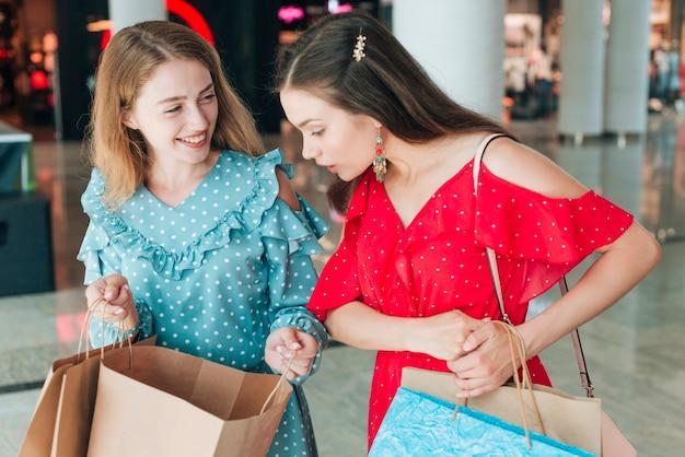 ミディアムショットの女の子が自分の買い物袋をチェック 無料写真