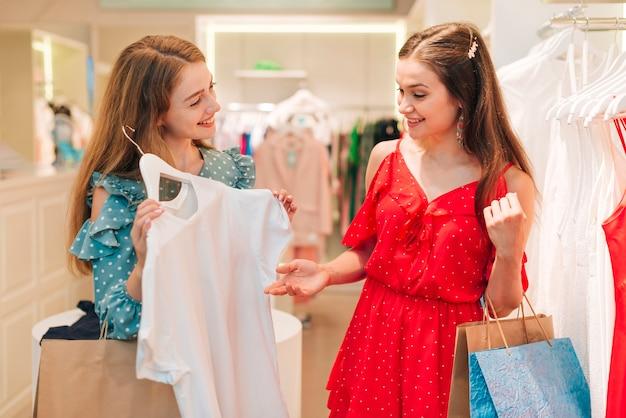 ファッションの女の子が店で服をチェック 無料写真