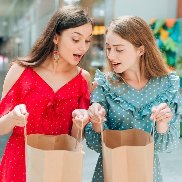 買い物袋を見て驚いた友達 無料写真