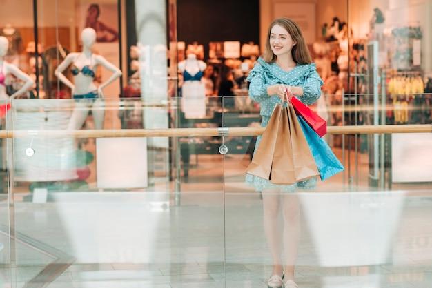 モールでドレスを着たロングショットの女の子 無料写真