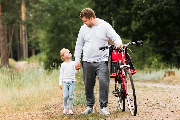 Отец и дочь гуляют рядом с велосипедом Бесплатные Фотографии