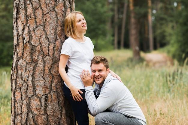 夫の妻の妊娠中の腹を聞いて 無料写真