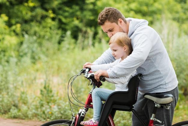 Заботливый отец держит дочь на велосипеде Бесплатные Фотографии