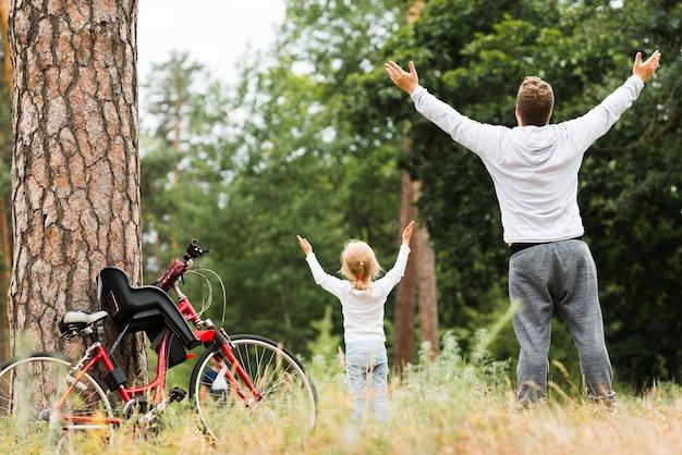 空気中の手で立っている父と娘 無料写真
