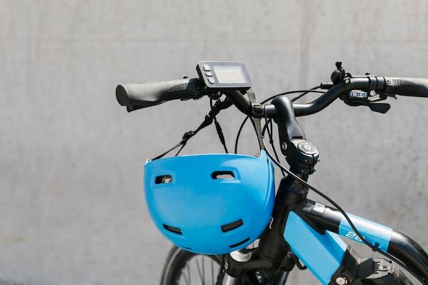 Крупным планом электронный велосипед с шлемом на руле Бесплатные Фотографии