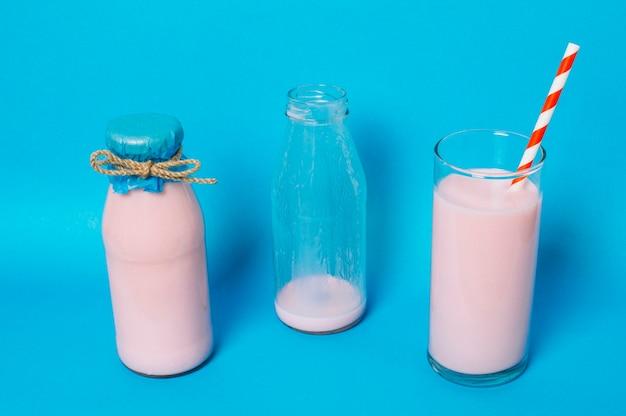 空のボトルと満杯の横にあるピンクのスムージー 無料写真
