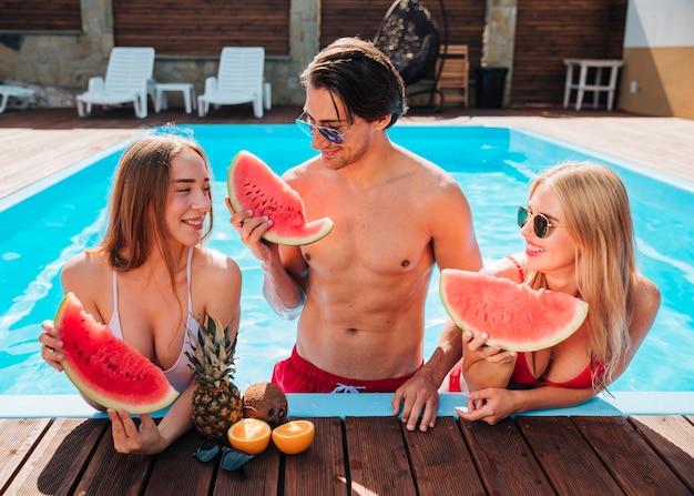 正面の友達がプールでスイカを食べる 無料写真