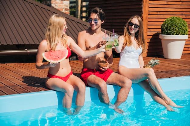 ロングショットの友人がプールでカクテルを楽しんで 無料写真