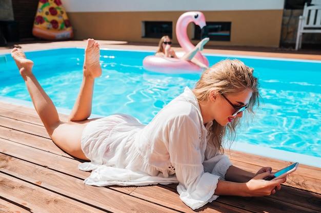ロングショットの女性がプールで彼女の電話をチェック 無料写真