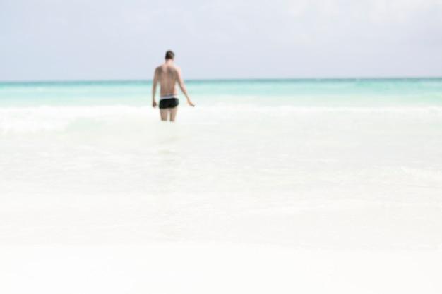 海を歩いて男のロングショット 無料写真