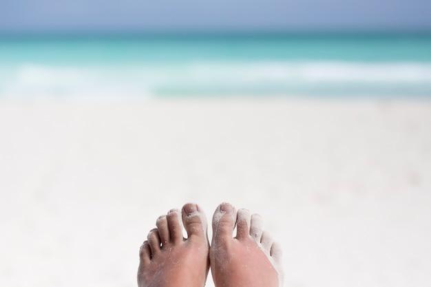 浜の砂で覆われた足のクローズアップ 無料写真