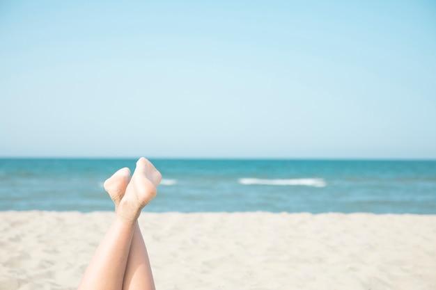 海辺で女性の足を閉じる 無料写真