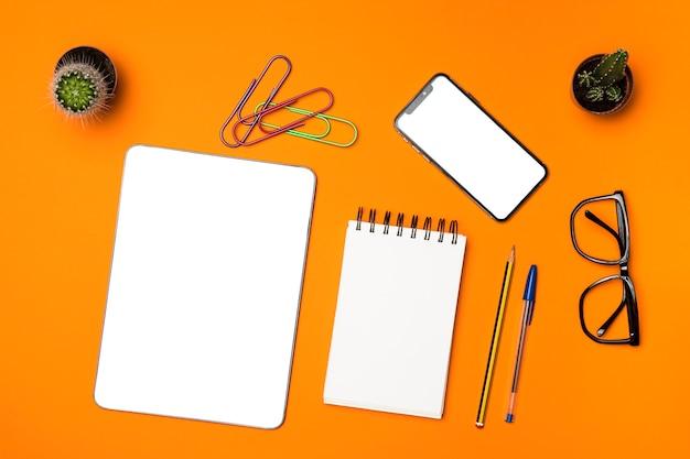 オレンジ色の背景とフラットレイアウトデスクコンセプト 無料写真