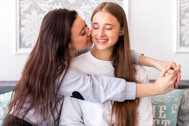 彼女のガールフレンドにキス若いブルネット 無料写真