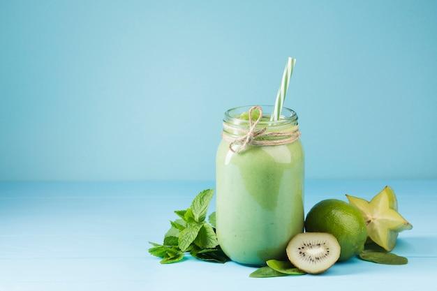 青い背景を持つ緑のスムージーの瓶 無料写真