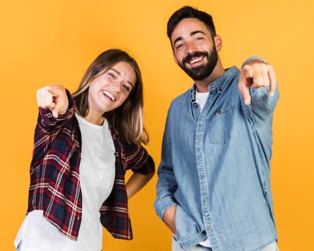 ミディアムショットカップル、カメラを指して 無料写真
