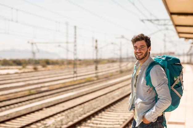 電車を待っている笑みを浮かべて男 無料写真