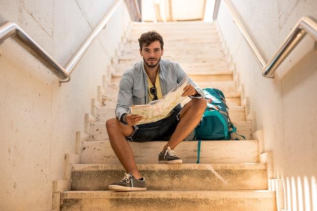 カメラ目線の階段に座っている旅行者 無料写真
