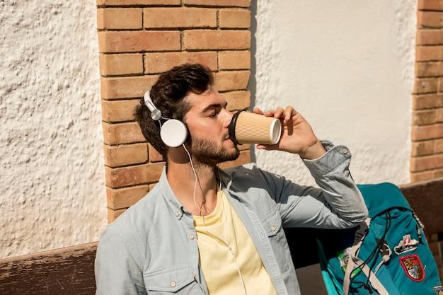 ミディアムショットトラベラーがコーヒーを飲む 無料写真
